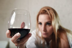 Sad depressed alcoholic drunk woman drinking at home in housewife alcohol abuse and alcoholism. Blond sad and wasted alcoholic woman sitting at home sofa couch royalty free stock images