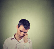 Sad, depressed, alone, man resting his head on hand looking down Stock Photos