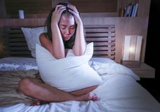 Sad and depressed Asian Korean woman in bed suffering depression anxiety and insomnia feeling miserable. Young beautiful sad and worried Asian Korean woman awake Royalty Free Stock Photos