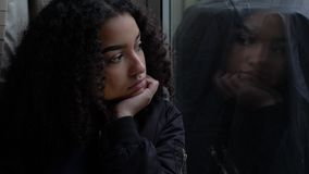 Sad depressed beautiful female mixed race African American girl teenager young woman teen looking out of a window
