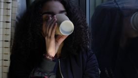 Girl teenager young woman teen wearing a black jacket sitting looking out of a window and drinking cup of coffee stock footage
