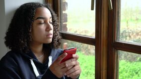 Sad or depressed beautiful mixed race African American girl teenager using her cell phone for social media