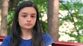 Sad, depressed beautiful teenager girl. Sitting on bench in park stock footage