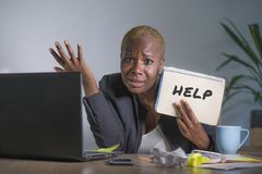 Sad and depressed black afro American woman suffering stressed at office working with laptop computer feeling overwhelmed asking f. Or help holding notepad in stock photos
