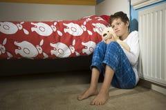Sad and depressed boy on bedroom Royalty Free Stock Photos
