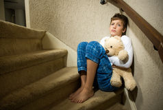 Sad and depressed boy in corner. A sad and depressed boy is sitting in the corner of a staircase Stock Photos
