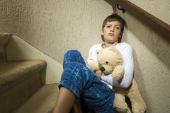 Sad and depressed boy in corner. A sad and depressed boy is sitting in the corner of a staircase Royalty Free Stock Photography