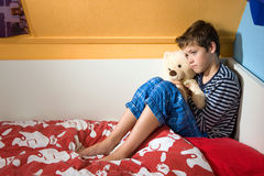 Sad and depressed boy on his bed Stock Photography