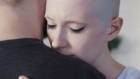 Sad, depressed cancer patient woman hugging her supporting husband