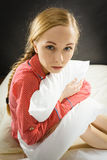 Sad depressed girl in bed gripping pillow Stock Photos