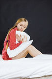 Sad depressed girl in bed gripping pillow Royalty Free Stock Images