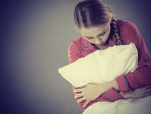 Sad depressed girl in bed gripping pillow Stock Photography