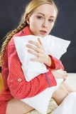 Sad depressed girl in bed gripping pillow. Mental health depression insomia concept. Sad depressive young woman teen blonde girl wearing red pajamas sitting on Stock Images