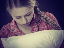 Sad depressed girl in bed gripping pillow. Mental health depression insomia concept. Sad depressive young woman teen blonde girl wearing red pajamas sitting on Stock Photos