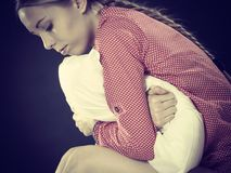 Sad depressed girl in bed gripping pillow. Mental health depression insomia concept. Sad depressive young woman teen blonde girl wearing red pajamas sitting on Stock Photography