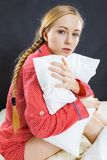 Sad depressed girl in bed gripping pillow. Mental health depression insomia concept. Sad depressive young woman teen blonde girl wearing red pajamas sitting on Royalty Free Stock Photography