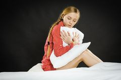 Sad depressed girl in bed gripping pillow. Mental health depression insomia concept. Sad depressive young woman teen blonde girl wearing red pajamas sitting on Royalty Free Stock Image