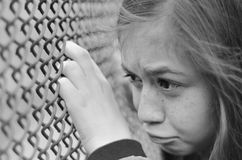 Sad depressed girl with rusty fence - black and white royalty free stock image