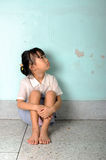 Sad and depressed little girl sitting near the wall Stock Photo