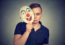 Man wearing clown mask pretending stock image