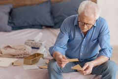 Sad depressed man holding a note. Message from the past. Sad depressed elderly man holding an envelope and reading an old note while thinking about his past Stock Images