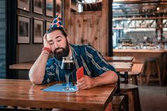 Sad depressed man sitting in nice pub on his birthday alone. Lonely birthday. Sad depressed man feeling only sad emotions while sitting in nice pub on his royalty free stock photos