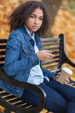 Sad Depressed Mixed Race African American Teenager Using Cell Ph. Beautiful mixed race African American girl teenager female young woman using cell phone and Stock Photo