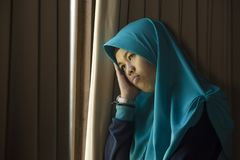 Sad and depressed Muslim woman in Islam traditional Hijab head scarf at home window feeling unwell suffering depression crisis and. Lifestyle portrait of young royalty free stock images