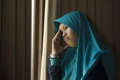 Sad and depressed Muslim woman in Islam traditional Hijab head scarf at home window feeling unwell suffering depression crisis and. Lifestyle portrait of young stock image