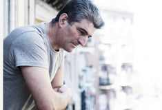 Sad and depressed 40s man looking through outdoors at home balco Royalty Free Stock Images