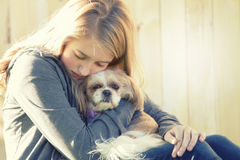 A sad or depressed teenage girl hugging a small dog. In an outdoor setting stock photos