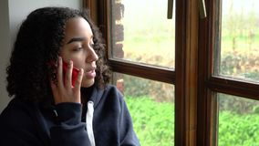 Sad depressed unhappy biracial mixed race African American girl teenager young woman sitting by a window phone call talking on her stock video footage