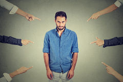 Sad depressed upset man looking down many fingers pointing at him Stock Photo