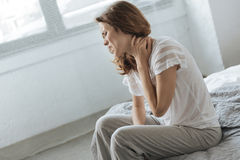 Sad depressed woman suffering from neck inflammation. Feeling of pain. Sad depressed unhappy woman holding her neck and feeling pain while suffering from neck stock photo