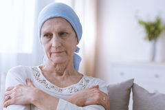 Depressed woman suffering from cancer. Sad depressed women suffering from malignant breast cancer sitting alone Royalty Free Stock Images