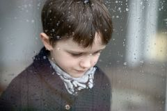 Sad depressed 7 year old boy standing by the window royalty free stock photography