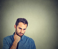 Sad depressed young man holding head with hand looking down Stock Image