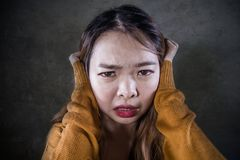 Sad and desperate Asian Korean woman holding her head depressed feeling anguish and pain on isolated dark background in pain face. Young crazy desperate and sad royalty free stock images