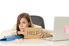 Sad desperate businesswoman in stress at office computer desk holding help sign. Young attractive sad and desperate businesswoman suffering stress at office Royalty Free Stock Photo