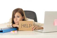 Sad desperate businesswoman in stress at office computer desk holding help sign Royalty Free Stock Images