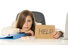 Sad desperate businesswoman in stress at office computer desk holding help sign. Young attractive sad and desperate businesswoman suffering stress at office Royalty Free Stock Images