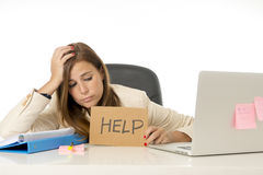 Sad desperate businesswoman in stress at office computer desk holding help sign. Young attractive sad and desperate businesswoman suffering stress at office Stock Image