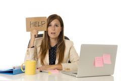 Sad desperate businesswoman in stress at office computer desk holding help sign Stock Photography