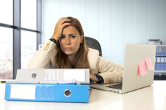 Sad and desperate businesswoman suffering stress and headache at office laptop computer desk Stock Photos