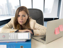 Sad and desperate businesswoman suffering stress and headache at office laptop computer desk Stock Photography