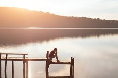 Give up, sad desperate man sitting alone, problems and solitude, failure concept. Sad desperate man sitting on pier alone, problems and solitude, failure concept Royalty Free Stock Photo
