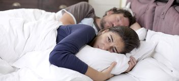 Sad desperate woman in bed while husband is sleeping Stock Image