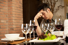Sad Dinner Date. Asian Man is upset over dinner date Royalty Free Stock Photography