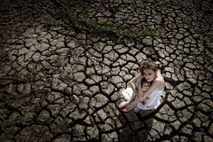 Sad dirty woman is at cracked earth desert Stock Photography