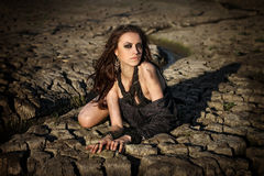 Sad dirty woman is at cracked earth desert Royalty Free Stock Image